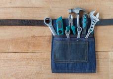 Оборудуйте пояс с инструментами на предпосылке деревянной доски стоковое изображение