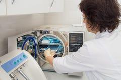 Оборудуйте стерилизацию в зубоврачевании, instrumenst загрузки медсестры в стерилизаторе стоковые изображения