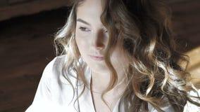 Обольстительная девушка в nighty волосы усмехаясь, бросать и представляя на кровати медленно сток-видео