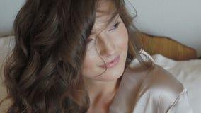 Обольстительная девушка в nighty волосы усмехаясь, бросать и представляя на кровати медленно акции видеоматериалы