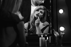 Обольстительная женщина кладя на губную помаду Стоковые Изображения