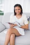 Обольстительная молодая темная с волосами женщина в белых одеждах читая кассеты Стоковое Изображение RF