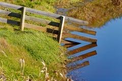 Обрабатывайте землю загородка достигая в воду стоковое изображение