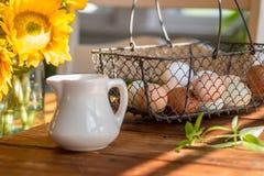 Обрабатывайте землю свежие яичка в корзине провода на деревянной столешнице стоковые фотографии rf