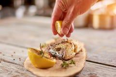 Обрабатывать зажаренных рыб с лимонным соком стоковые фотографии rf