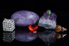 Обработанный аметист, кристалл горы и другие камни и ювелирные изделия на темной предпосылке с отражением Стоковая Фотография