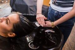 Обработка волос курорта, парикмахер прикладывает белую маску к волосам клиентов длинным темным Курорт, забота, красота и люди Стоковые Изображения