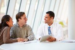 Обработка доктора Используя Таблетки Компьютера Discussing с пациентами Стоковые Фотографии RF