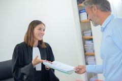 Обработка документов будучи проведенным между юристом и клиентом Стоковая Фотография