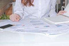 Обработка документов или диаграммы на столе в офисе с работником Стоковые Изображения