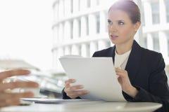 Обработка документов обсуждения коммерсантки с коллегой в столовой офиса Стоковые Изображения
