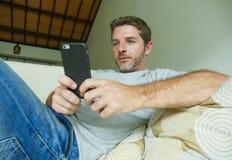 Образа жизни портрет внутри помещения молодого счастливого и привлекательного кресла софы человека дома используя средства массов стоковая фотография