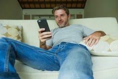 Образа жизни портрет внутри помещения молодого счастливого и привлекательного кресла софы человека дома используя средства массов стоковая фотография rf