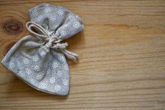 Образец открытки, нейтральный серый мешок подарка на деревянной предпосылке с свободным copyspace для приветствуя текста Стоковые Фото