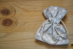Образец открытки, нейтральный серый мешок подарка на деревянной предпосылке с свободным copyspace для приветствуя текста Стоковое Изображение RF