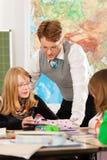 Образование - зрачки и учитель уча на школе Стоковые Фото