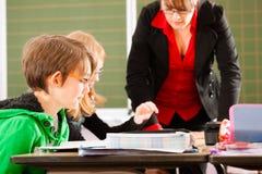 Образование - зрачки и учитель уча на школе Стоковые Изображения RF