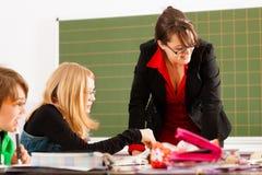Образование - зрачки и учитель уча на школе Стоковое Изображение