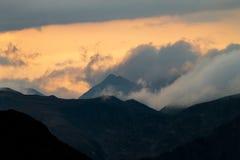 Образование облака окружает горы на заходе солнца стоковые фото
