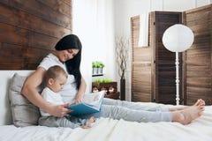 Образование ребенка Счастливая мать при ее малыш сидя на кровати и читая книгу Стоковое Изображение