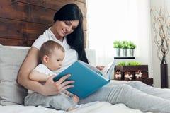 Образование ребенка Счастливая мать при ее малыш сидя на кровати и читая книгу Стоковые Изображения RF