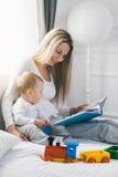 Образование ребенка Счастливая мать при ее малыш сидя на кровати и читая книгу Стоковое фото RF