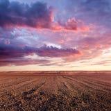 Образования обрабатываемых земель и облака на заходе солнца Стоковое Фото