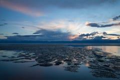 Образования перемещаясь льда на воде отделывают поверхность на заходе солнца Стоковые Изображения