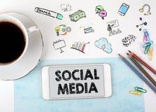 образуйте переговоры принципиальной схемы связи имея social людей средств Мобильный телефон и кофейная чашка на белом столе офиса Стоковое Фото