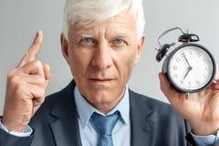 Образ жизни дела Положение бизнесмена изолированное на сером показывая времени на будильнике указывая вверх по серьезному концу-в стоковая фотография rf
