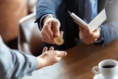 Образ жизни дела Торговец сидя на кафе с чашкой кофе оплачивая для счета к официанту с концом монетки cryptocurrency стоковые изображения rf