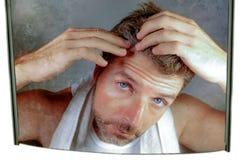 Образ жизни изолировал портрет привлекательного потревоженного и, который отнесенного кавказского человека смотря зеркало ванной  Стоковые Изображения RF