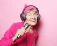 Образ жизни и концепция людей: Музыка смешной пожилой женщины слушая с наушниками и петь с mic над розовой предпосылкой стоковое фото rf