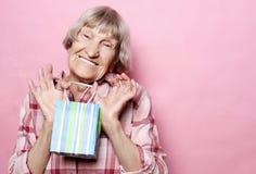 Образ жизни и концепция людей: Счастливая старшая женщина с хозяйственной сумкой над розовой предпосылкой стоковые изображения