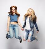 Образ жизни и концепция людей: Счастливые девушки скача над белым bq Стоковая Фотография