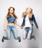 Образ жизни и концепция людей: Счастливые девушки скача над белым bq Стоковые Фотографии RF