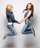Образ жизни и концепция людей: Счастливые девушки скача над белым bq Стоковые Изображения RF
