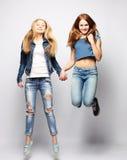 Образ жизни и концепция людей: Счастливые девушки скача над белым bq Стоковое Изображение