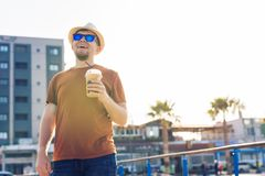 Образ жизни, пить и концепция людей - человек в солнечных очках выпивая frappe кофе от устранимого бумажного стаканчика outdoors Стоковая Фотография RF