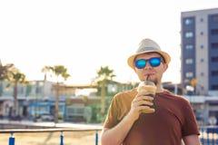 Образ жизни, пить и концепция людей - человек в солнечных очках выпивая frappe кофе от устранимого бумажного стаканчика outdoors Стоковые Изображения RF