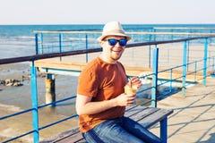 Образ жизни, пить и концепция людей - человек в солнечных очках выпивая frappe кофе от устранимого бумажного стаканчика outdoors Стоковое Изображение