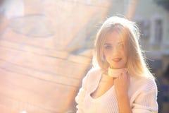 Образ жизни снятый довольной молодой женщины нося связанный свитер представляя на улице со слепимостью солнца стоковые изображения rf