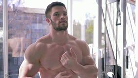 Образ жизни спорт, красивый сильный человек культуриста делает подогрев после разминки силы в строя мышце в фитнес-центре сток-видео