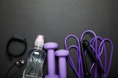 Образ жизни фитнеса, здоровых и активных Концепция спорт - гантели, браслет фитнеса, веревочка скачки, бутылка с водой, наушники  стоковое изображение rf