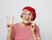 Образ жизни, эмоция и концепция людей: смешная бабушка с поддельными стеклами, смехом и готовым для партии стоковые фото