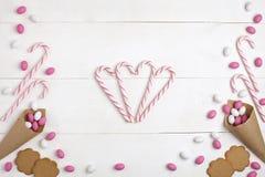 Обрамите конфеты, зефиры, печенья и Striped леденцы на палочке в форме предпосылки взгляд сверху сердца белой деревянной Стоковое Изображение RF