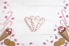 Обрамите конфеты, зефиры, печенья и Striped леденцы на палочке в форме предпосылки взгляд сверху сердца белой деревянной Стоковые Изображения RF