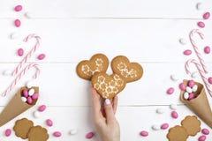 Обрамите конфеты и печенья в форме предпосылки взгляд сверху сердца белой деревянной Стоковые Фото