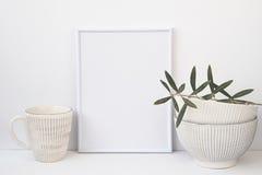 Обрамите модель-макет на белой предпосылке, ветви оливкового дерева, винтажных керамических шарах, кружке, copyspace для текста Стоковые Изображения RF