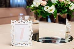 Обрамленный номер расположения около вазы с цветками стоковые изображения